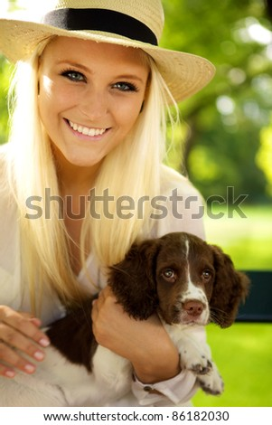 Young female sitting with a puppy on a park bench. - stock photo