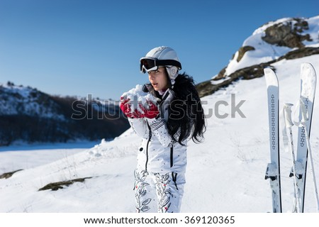 Young female skier in white snowsuit and helmet forming giant snowball in hands as she stands next to pair of upright skis - stock photo