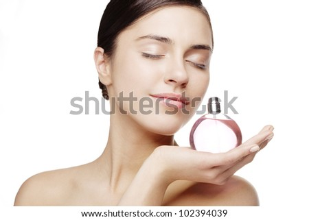 young female smelling a bottle of perfume - stock photo