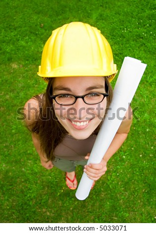 young female smiling architect or builder wearing a yellow hart hat holding architectural plans - stock photo