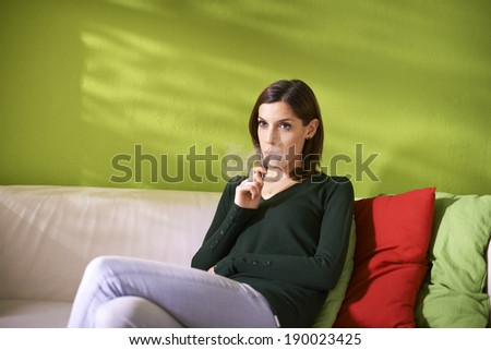young female smoker smoking e-cigarette at home, sitting on sofa and relaxing