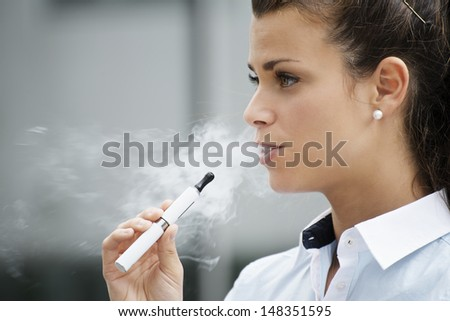 young female smoker smoking e-cigarette outdoors. Head and shoulders, side view - stock photo
