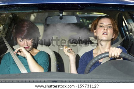 young female smoking while driving inside the car - stock photo
