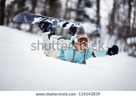 Young female snowboarder sliding down the slope on her belly, holding her hand out in front of her, like a superhero