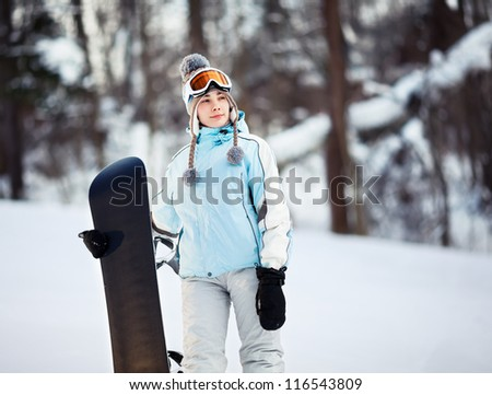 Young female snowboarder standing on ski slope holding her snowboard, she's looking away and smiling, copy space - stock photo