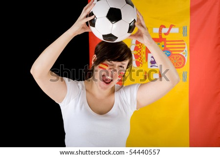 young female, spanish football team supporter with flag as background and small flags on her cheeks, holds football ball over her head, joy, enthusiasm