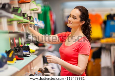 young female sportswear shop assistant working in store - stock photo