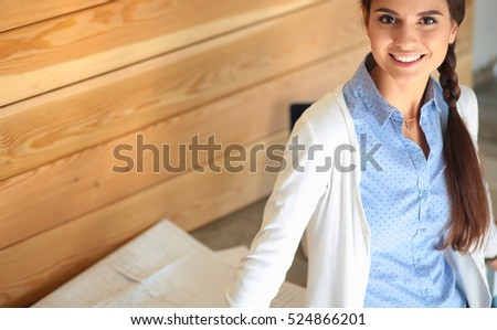 Young female standing near desk at home