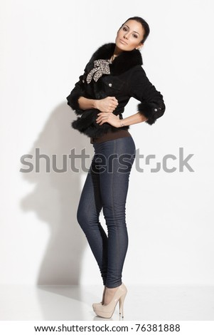 Young female standing near the white wall - stock photo