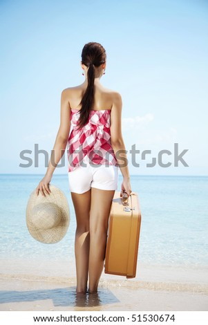 young female standing on the beach with retro suitcase