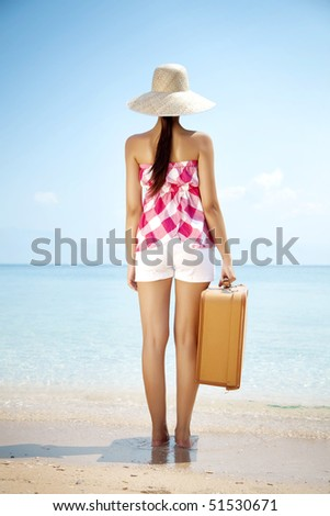 young female standing on the beach with vintage suitcase - stock photo