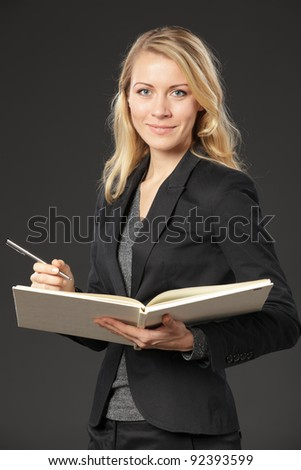 Young female standing with the opened book and a pen, isolated on grey background - stock photo