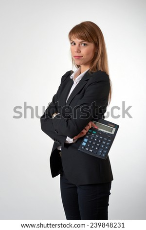 Young female staying and holding a calculator in her hand - stock photo