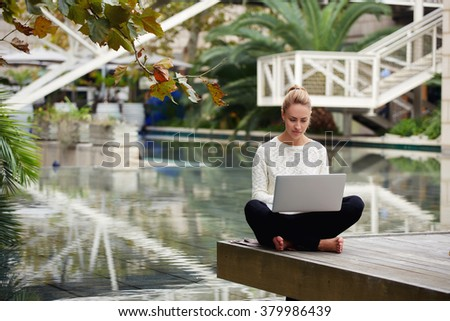 Young female student chatting with classmate via laptop computer while sitting on wooden pier near hotel, pretty woman checking email on net-book after walking in beautiful park in warm autumn day - stock photo