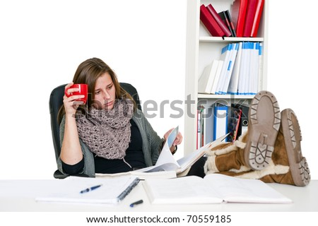 Young female student, dilligently reading her notes whilst studying with her feet on the desk and a cup in her hand, looking serious