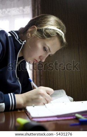 Young female student doing her homework - stock photo