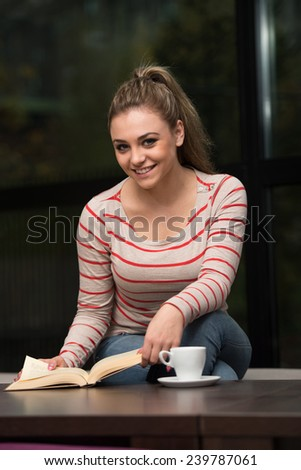 Young Female Student Drinking And Reading Book In Cafeteria - stock photo