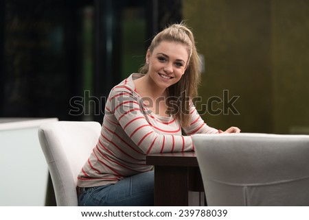 Young Female Student Drinking Cafe In Cafeteria - stock photo