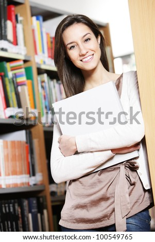 young female student holding book in library - stock photo