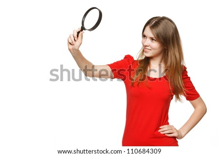 Young female student looking through the magnifying glass, isolated on white background - stock photo