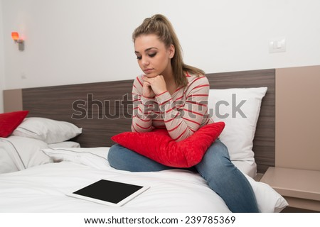 Young Female Student Lying On Bed And Having Fun With Touch Pad In Bedroom - stock photo