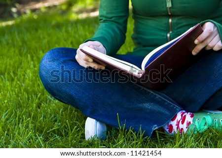 Young female student reading on the grass - stock photo