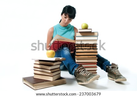 Young female student sitting and reading,apples on books - stock photo