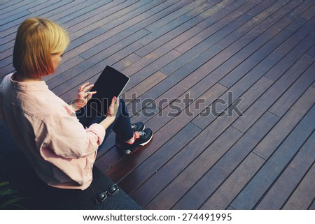 Young female student sitting in a university recreation hall using touch pad, freelancer girl working on her digital tablet with big copy space, hipster woman using touchscreen device in modern office - stock photo
