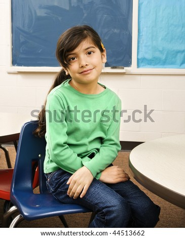 Young female student sitting in classroom. Vertically framed shot. - stock photo