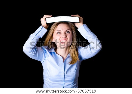 young female student thrilled and frightened trying to push the book into her head, learning concept, studio shoot isolated on black - stock photo