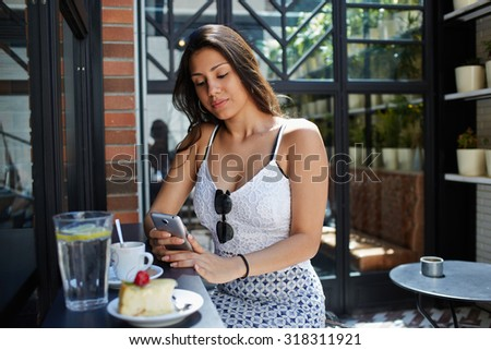 Young female student use mobile Internet on smart phone to correspond with her friends in chat,modern arabic women typing text message on cellphone while breakfast at sidewalk cafe in sunny summer day - stock photo