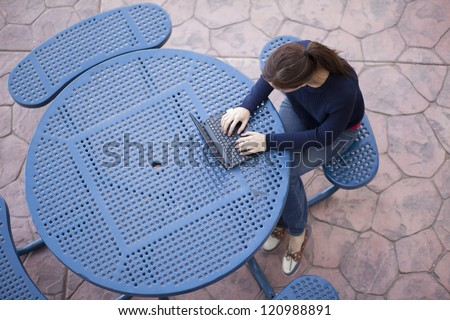 Young female student using a laptop at school - stock photo