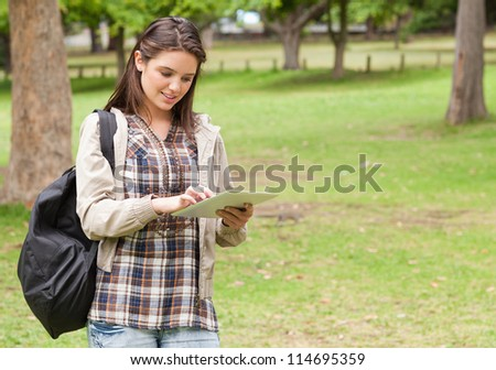 Young female student using a tactile tablet in a park - stock photo