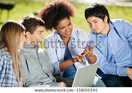 Young female student using mobilephone while classmates looking at it in campus - stock photo