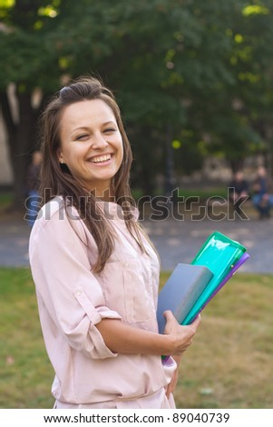 Young female student walks in the park,European, White, Caucasian, - stock photo