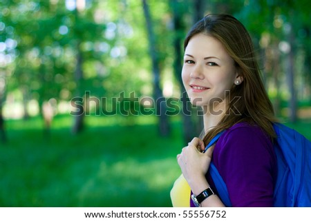 young female student with backpack walking in the park
