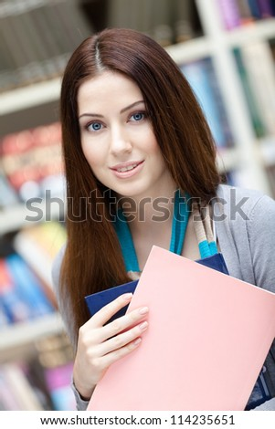 Young female student with books at the library. Research. Learning - stock photo