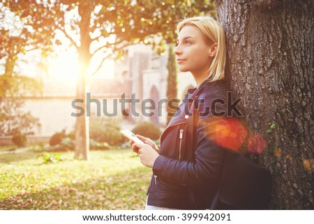 Young female student with cell telephone in hands is dreaming about something, while is standing on a campus. Thoughtful woman tourist is holding smart phone, while is enjoying free time in vacation - stock photo