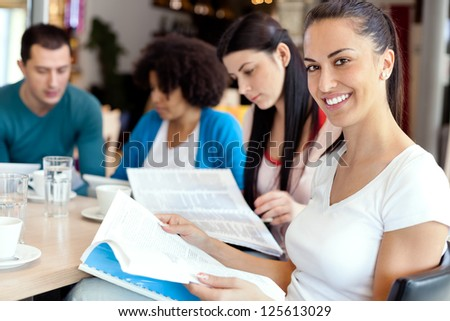 Young female student with friends on break at cafe - stock photo