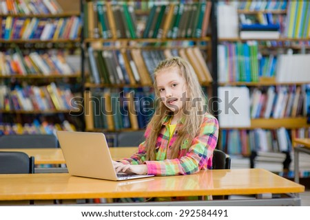 Young female student with laptop in library - stock photo