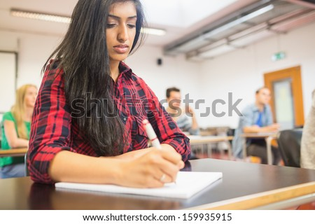 Young female student with others writing notes in the classroom - stock photo