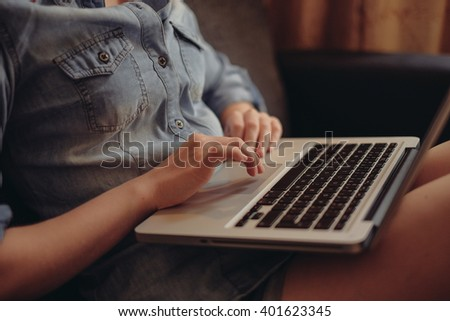 young female student working on her laptop at home