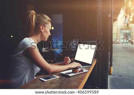 Young female student working on net-book with blank copy space screen for your text message or promotional content, cute woman successful freelancer using laptop computer while sitting in coffee shop  - stock photo