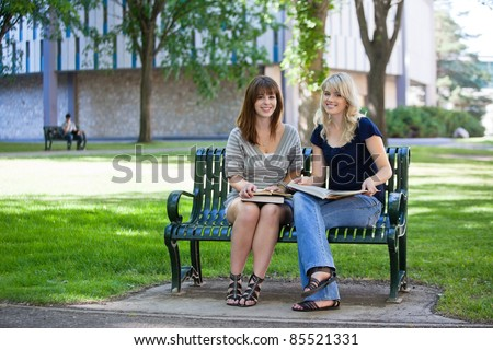 Young female students sitting on a bench on college campus - stock photo
