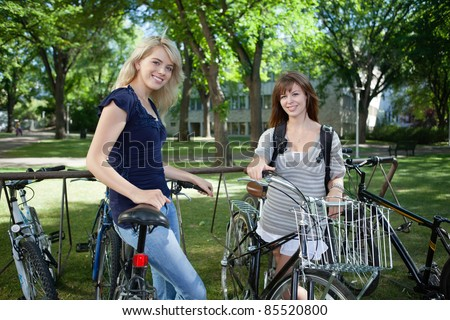 Young female students standing with bicycle at college campus lawn