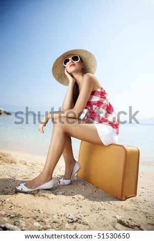 young female styled in 50s summer outfit sitting on a retro suitcase on the beach - stock photo