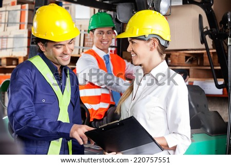 Young female supervisor communicating with foreman at warehouse - stock photo