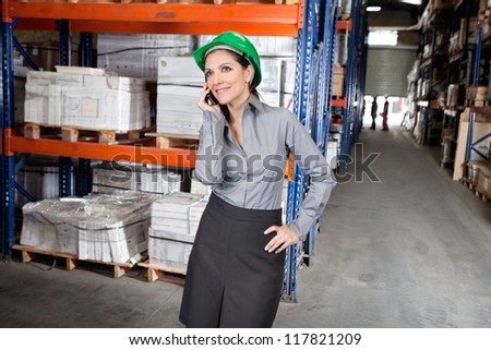 Young female supervisor in formals using cell phone at warehouse