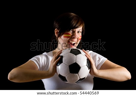 young female supporter with spanish flags on her cheeks, holds football ball, all isolated on black background