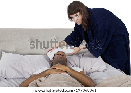 young female taking care of her sick boyfriend in bed - stock photo